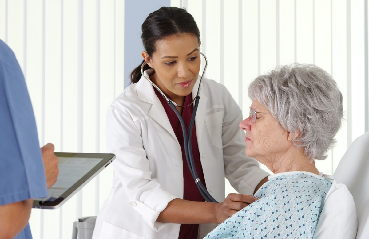 doctor listening to elderly patient's heart with stethoscope