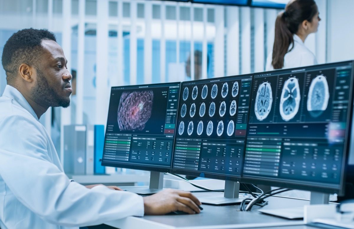 Medical Scientist Working with CT Brain Scan Images on a Personal Computer in Laboratory. Neurologists in Neurological Research Center Working on a Brain Tumor Cure