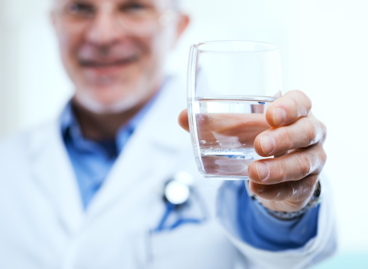 Doctor offering a glass of water