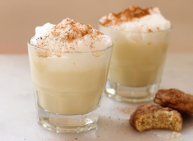 two cups of eggnog sprinkled with nutmeg next to two cookies