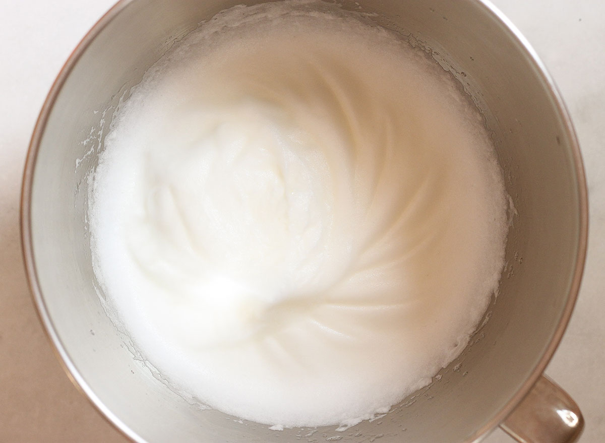 whisking egg whites in a large stainless steel bowl