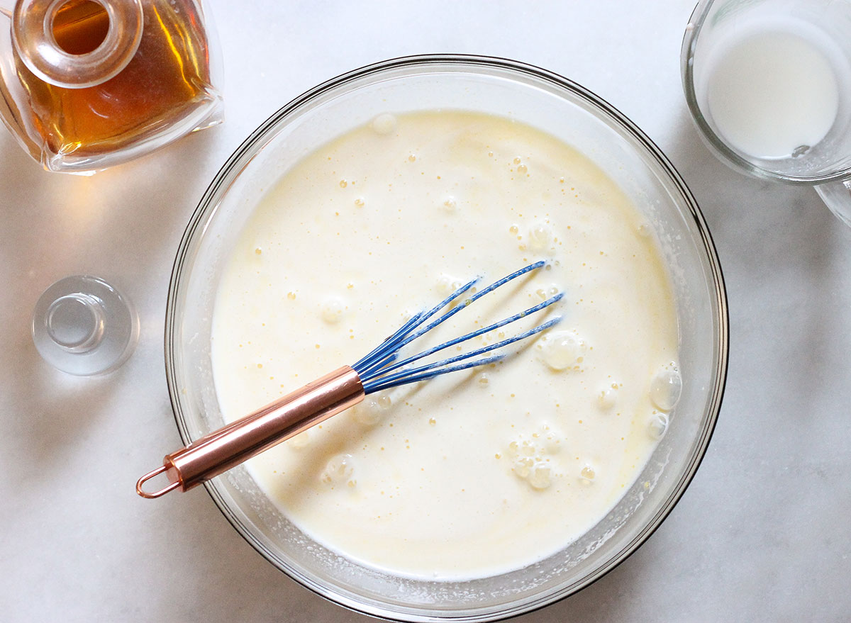 whisking egg mixture for eggnog with milk mixture and alcohol