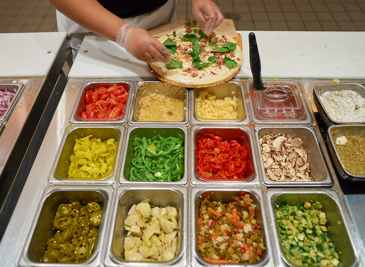 Serve making customized pizza at a fast casual restaurant