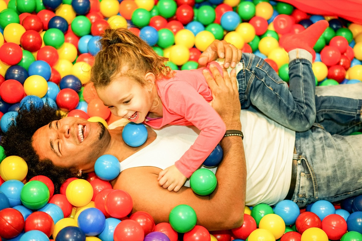 father playing with his daughter inside ball pit swimming pool
