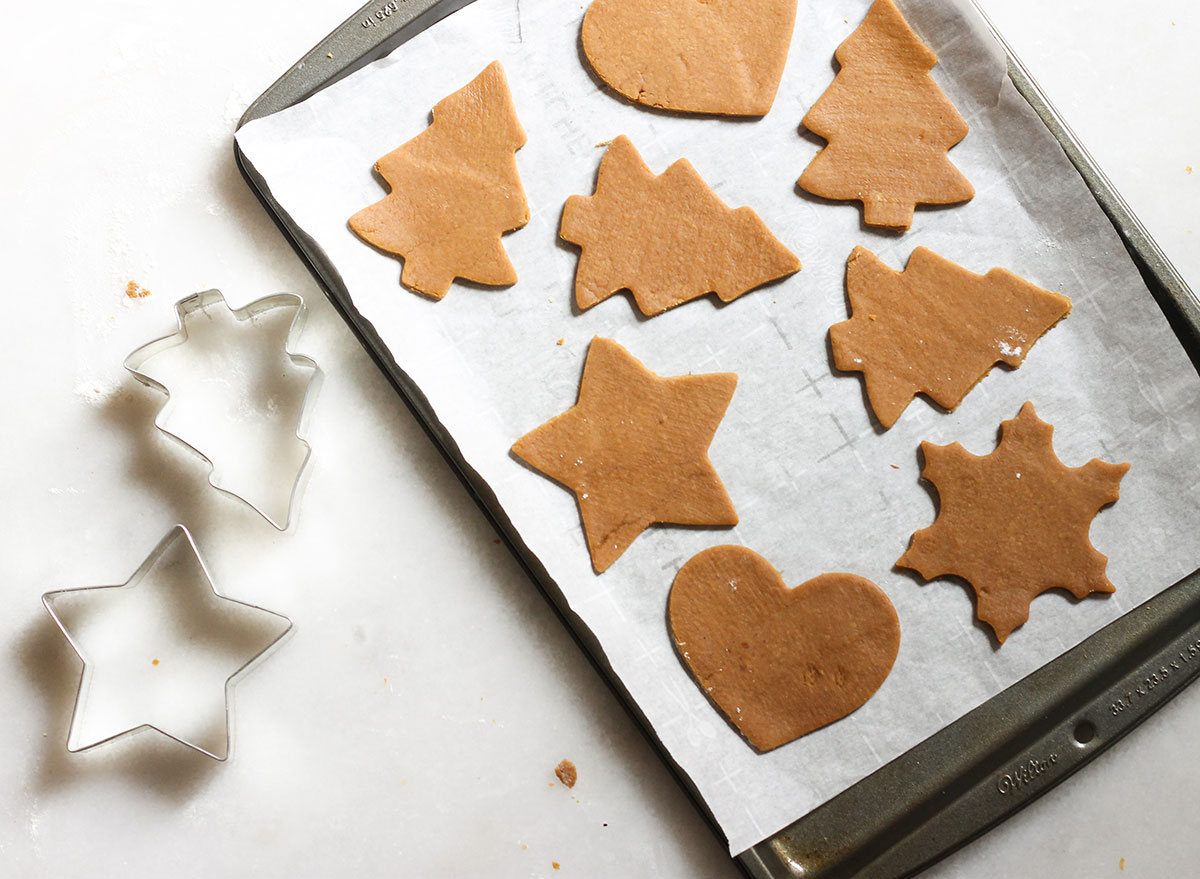 gingerbread cookies cut into shape on a baking sheet ready for the oven