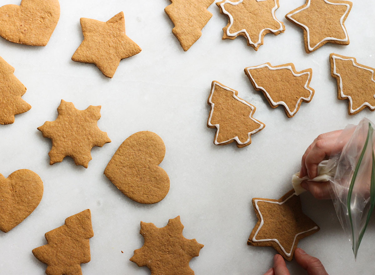icing the edges of gingerbread cookies on a marble counter