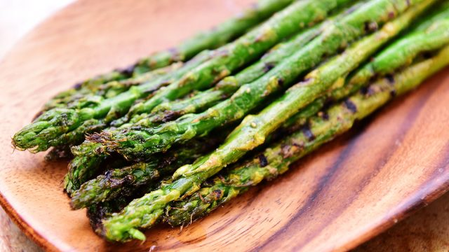 grilled asparagus on wooden surface