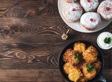 jelly donuts and latkes with dreidel on table