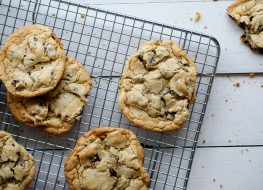 homemade chocolate chip cookies sitting cooling off on a drying rack