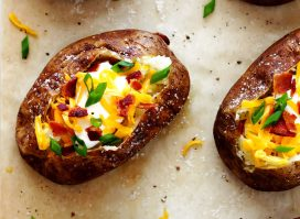 loaded baked potatoes on parchment paper with salt