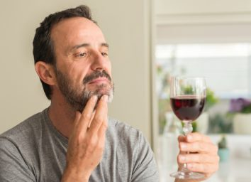 Middle age man drinking a glass of wine serious face thinking about question, very confused idea