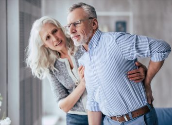 man is having back pain and his attractive old woman supports him