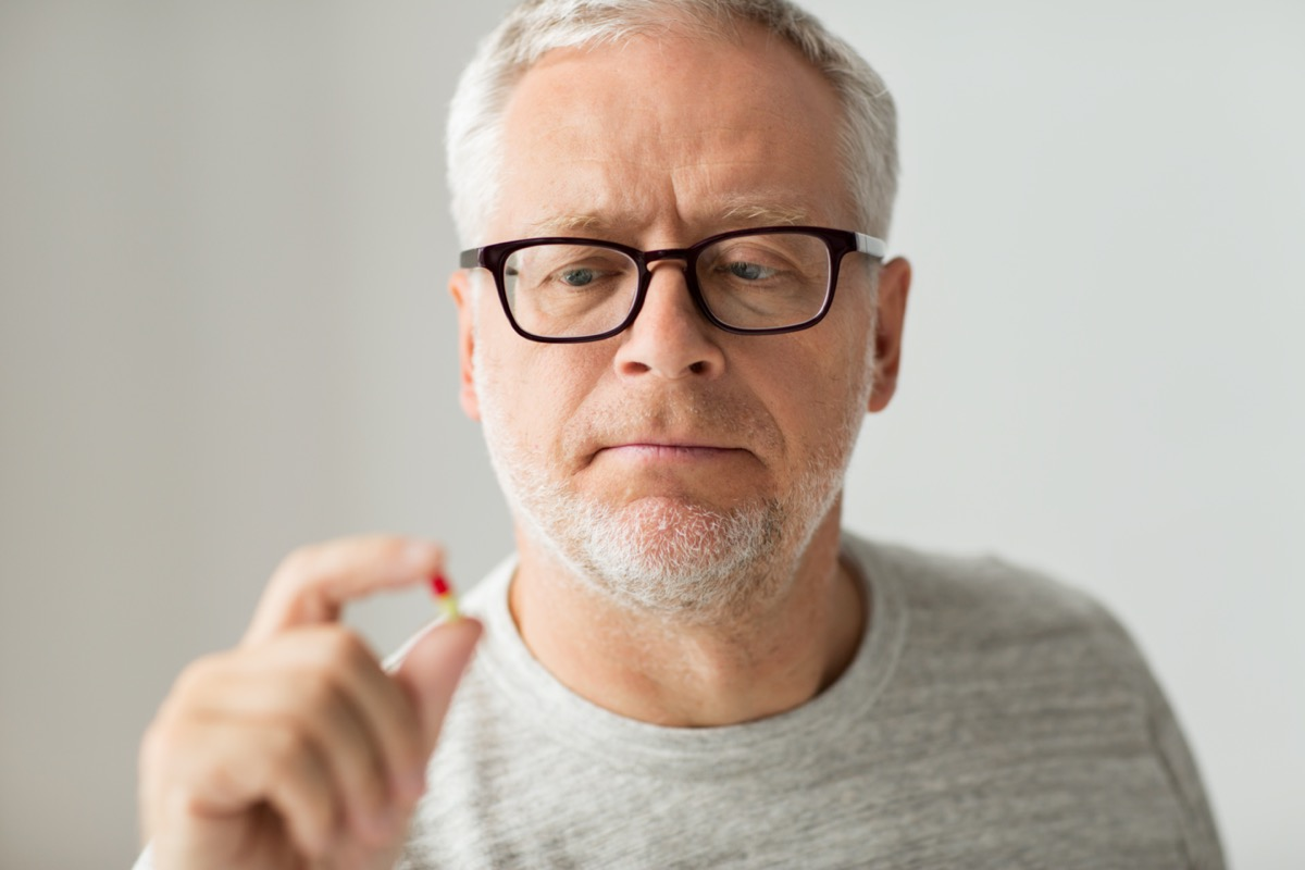 senior man taking medicine pill at home