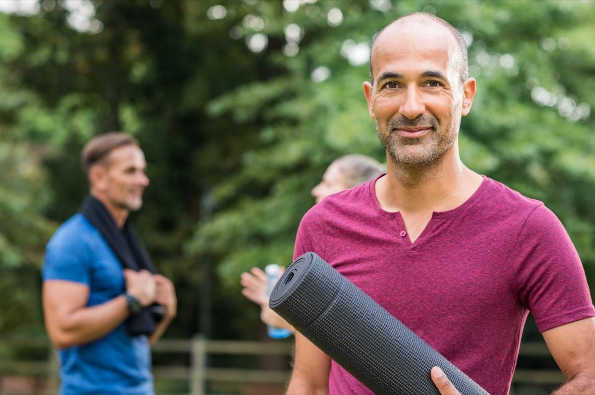 mature man holding yoga mat and looking at camera