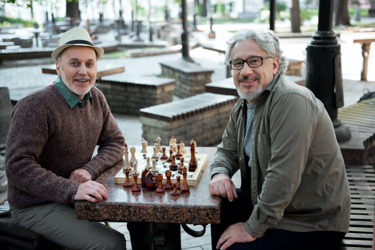 Glad mature pensioners relaxing near chessboard in park