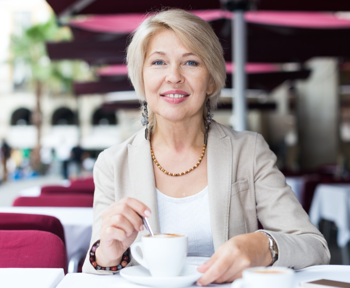mature female who is enjoying of lunch with coffee in cafe