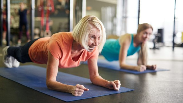 Mature blonde active woman standing in plank on mat during workout in contemporary fitness center.