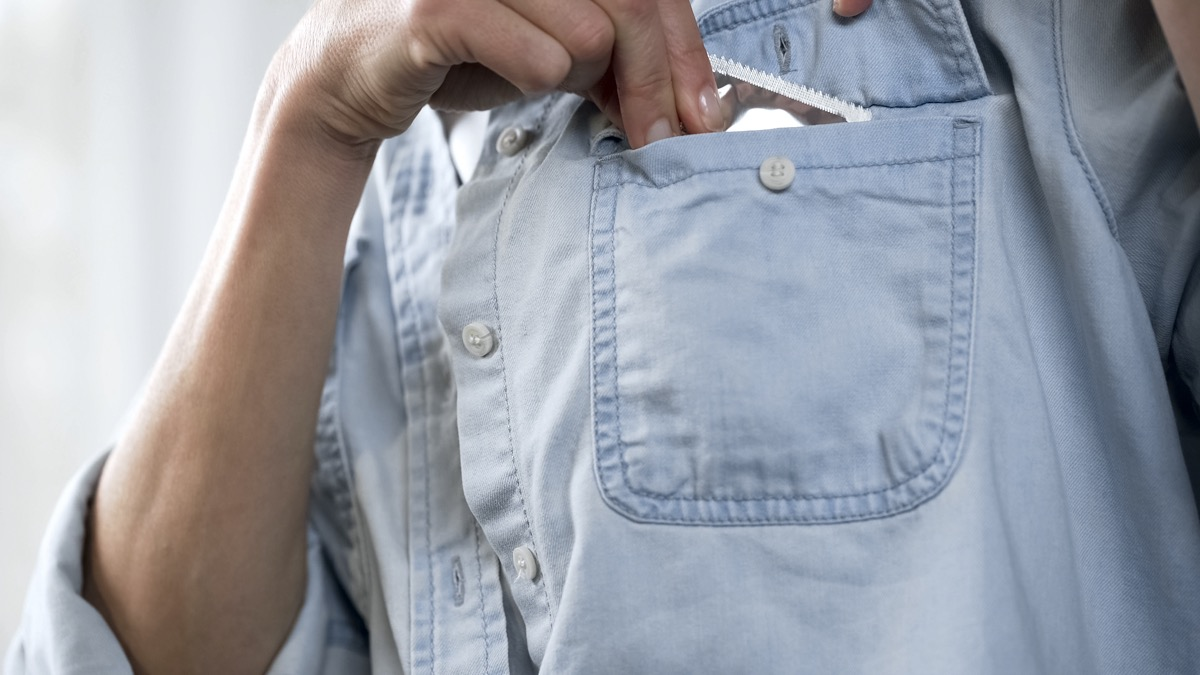 Womans hand putting condom package in her pocket, contraception
