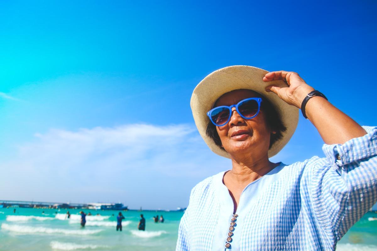 elderly women Wearing blue sunglasses Walking around the sea