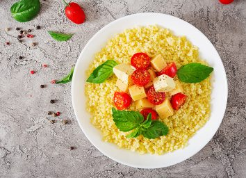 bowl of millet porridge with basil leaves cheese cubes and cherry tomato halves