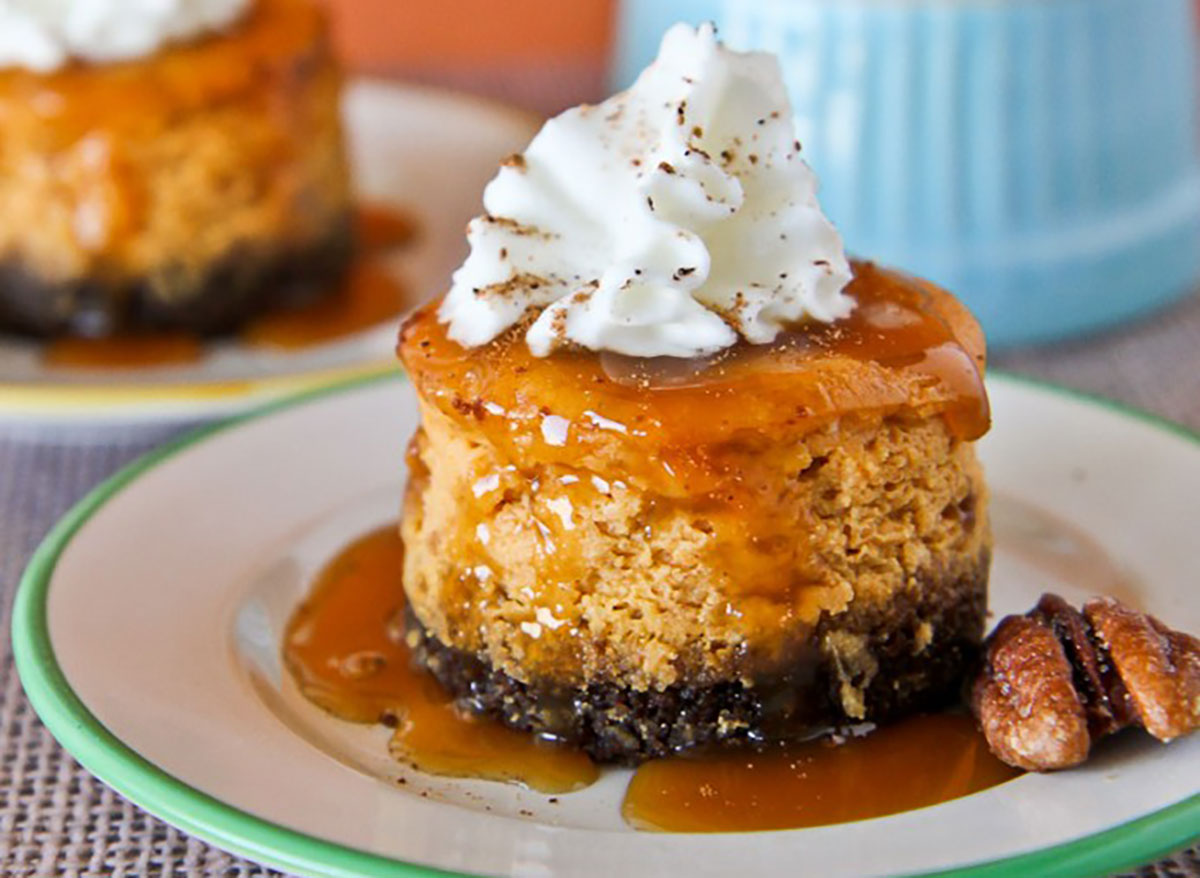 mini pumpkin cheesecake with gingersnap crust and pecan and whipped cream on plate