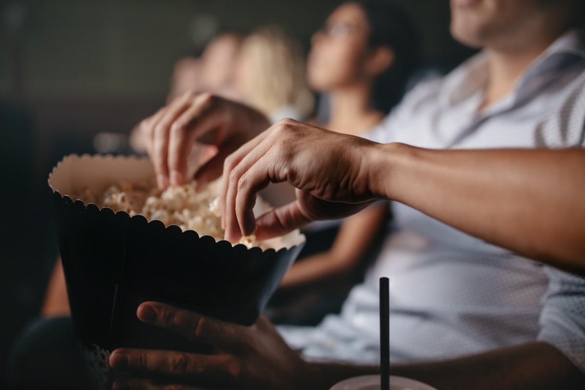 people eat popcorn in cinema, focus on hands