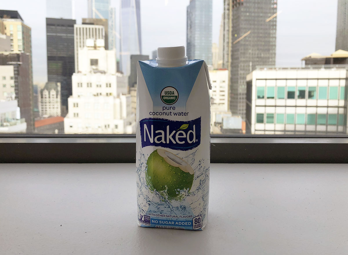 naked pure coconut water bottle by window