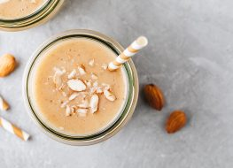 Protein shake with almonds and coconut shavings with a paper straw