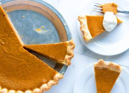pumpkin pie in metal baking dish with two slices on white dessert plates