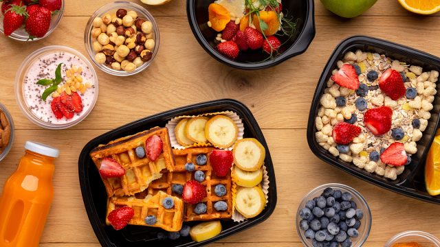 containers of ready made breakfast with strawberries blueberries waffles oatmeal chia pudding
