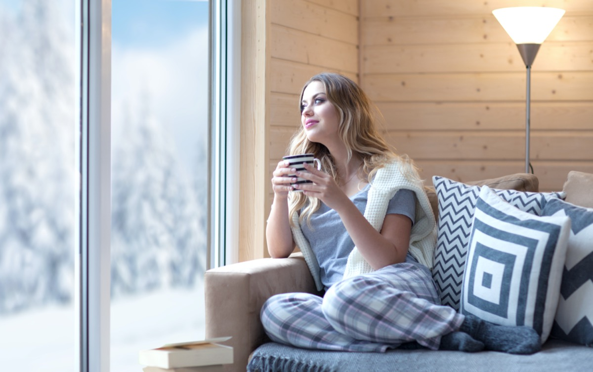 woman with cup of coffee sitting home in living room by the window. Winter snow landscape view