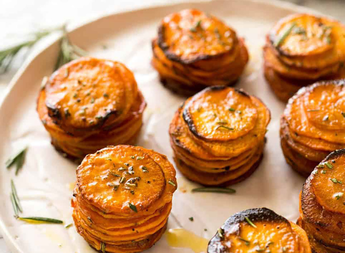 roasted sweet potato stacks of sliced potatoes on baking sheet with rosemary