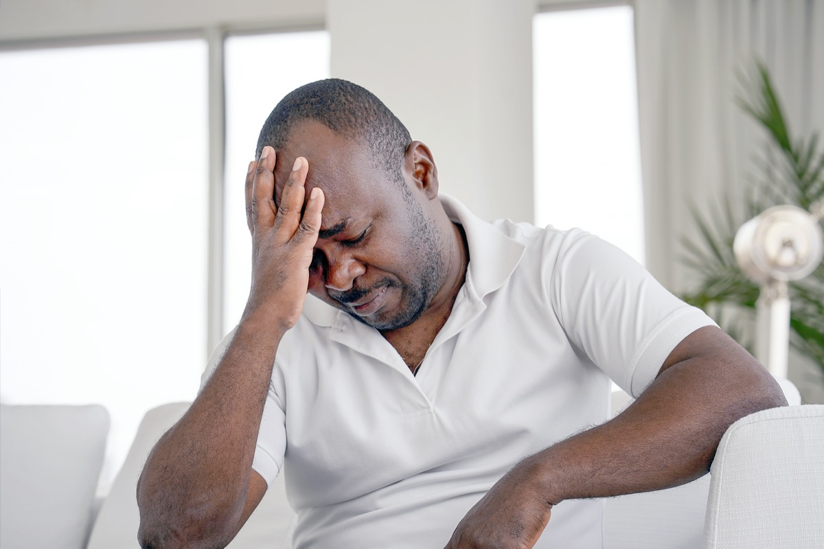 elderly Man suffering from headache migraine pain at home on sofa
