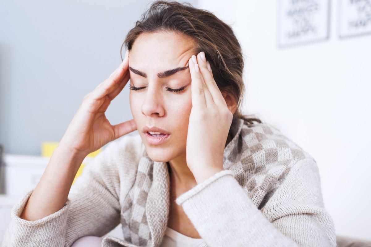 Woman with hard headache holding hands on head