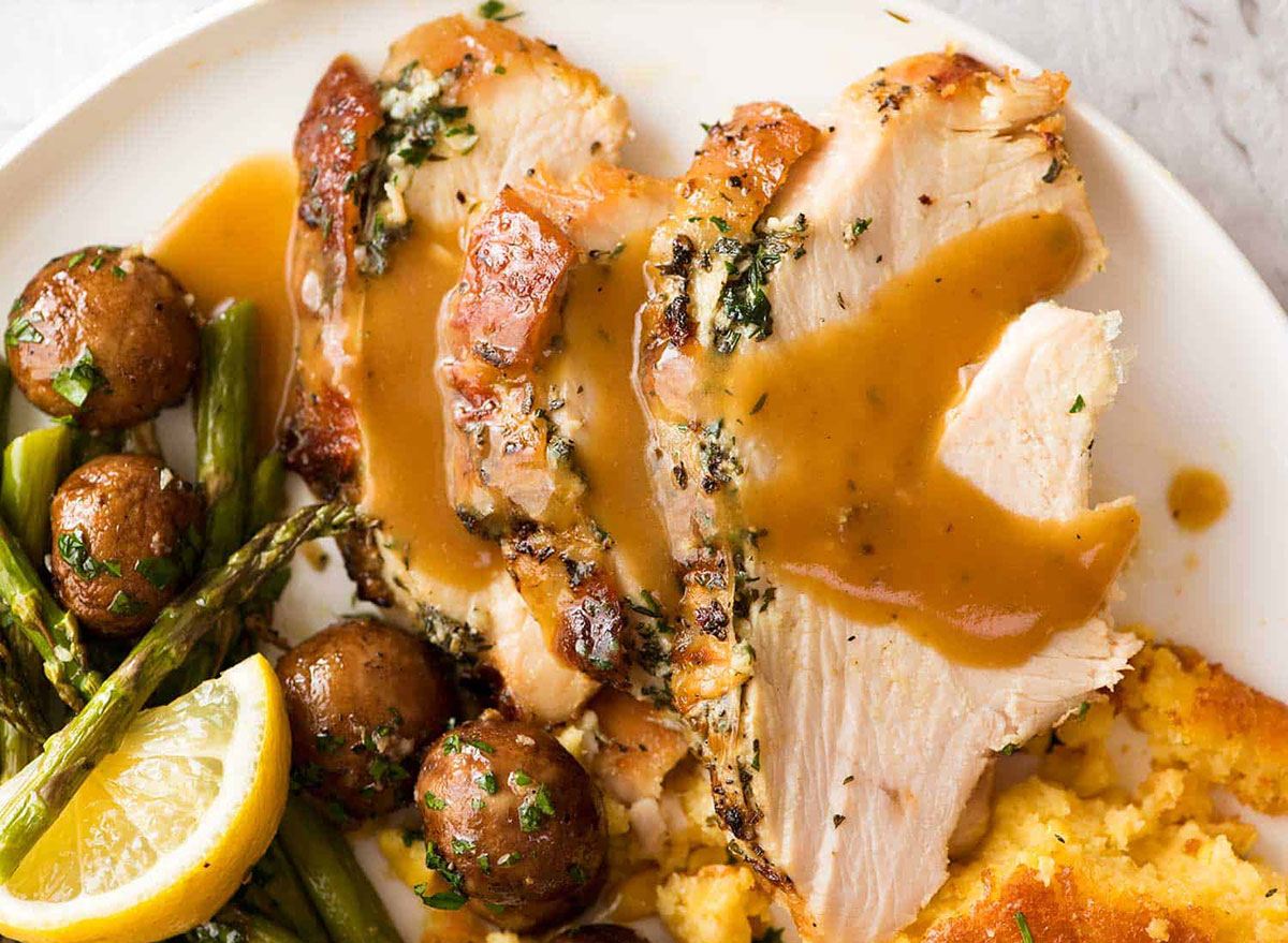 slow cooker turkey breast with gravy roasted mushrooms asparagus and lemon wedge
