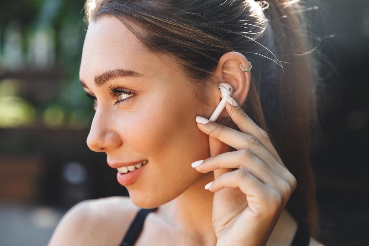 listening to music through wireless earphones outdoors