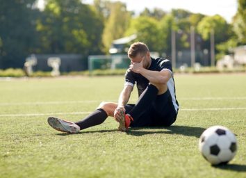 injured soccer player with ball on field
