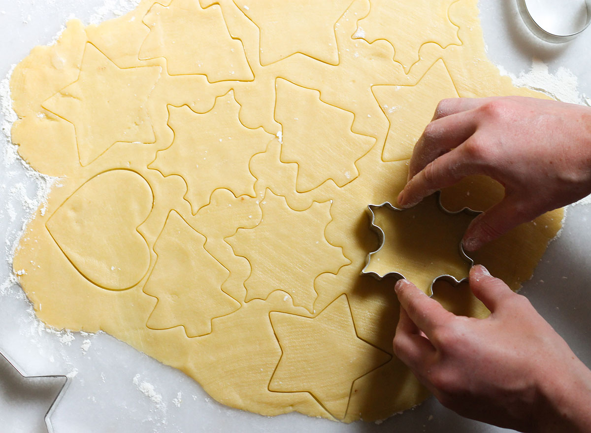 cutting sugar cookie shapes on a marble counter