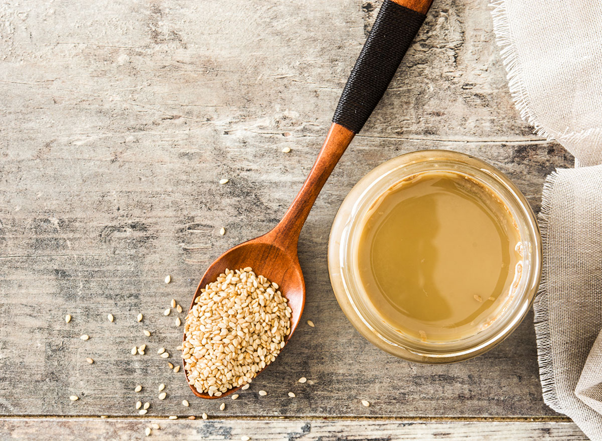 tahini in glass jar with wooden spoon