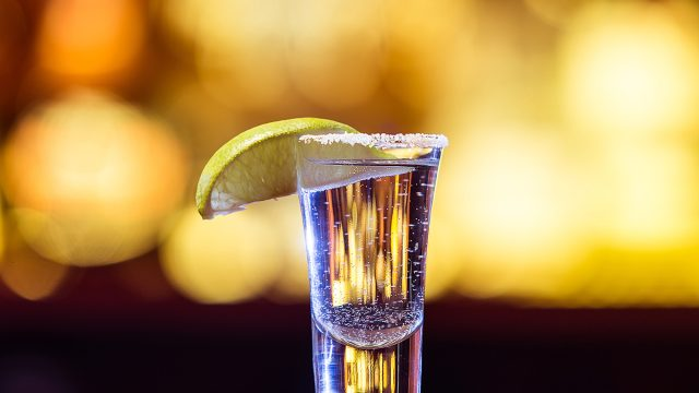 shot of tequila with salt rim and lime wedge