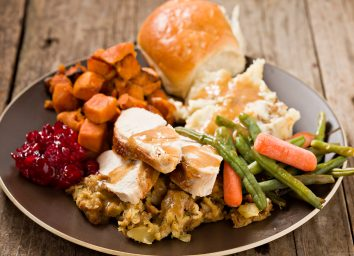 A high angle close up shot of a brown plate containing a bountiful thanksgiving turkey dinner. Shot on a grungy old wooden table