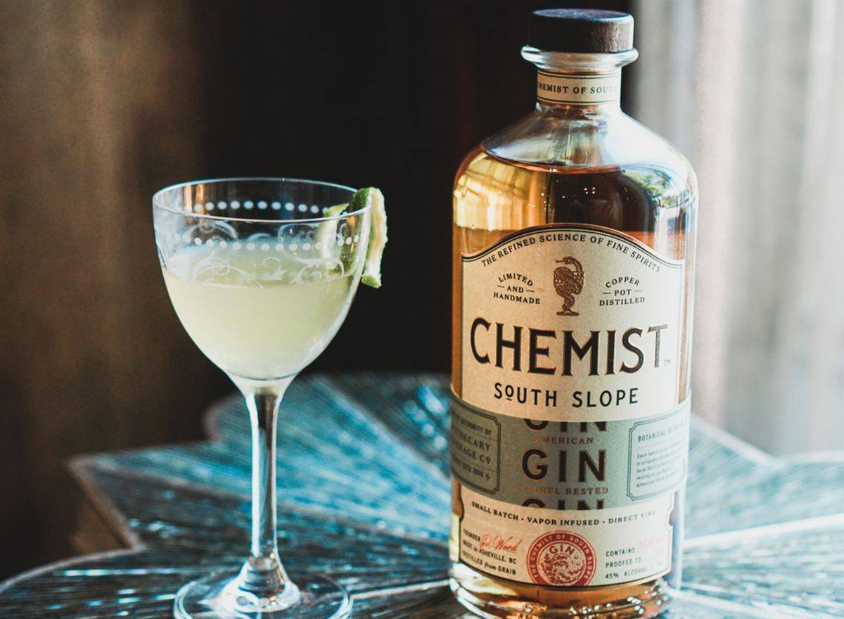 the chemist gin cocktail glass with bottle of housemade gin