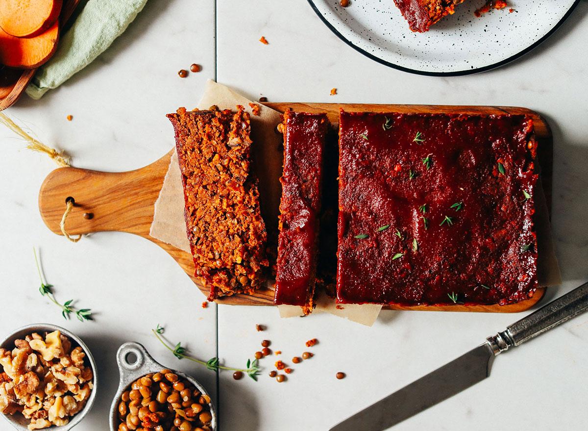 vegan lentil nut meatloaf slices on cutting board with nuts on the side