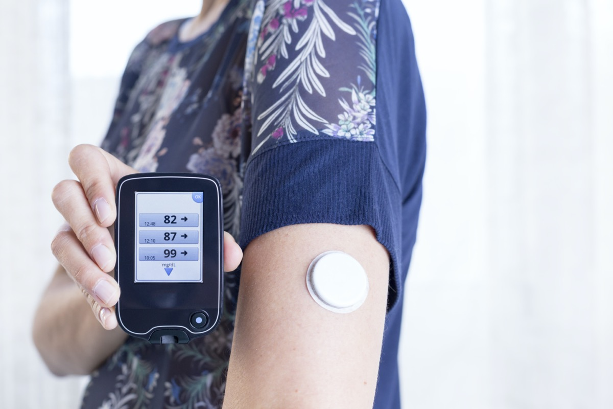 a hand of a young woman showing the reader after scanning the sensor of the glucose monitoring system