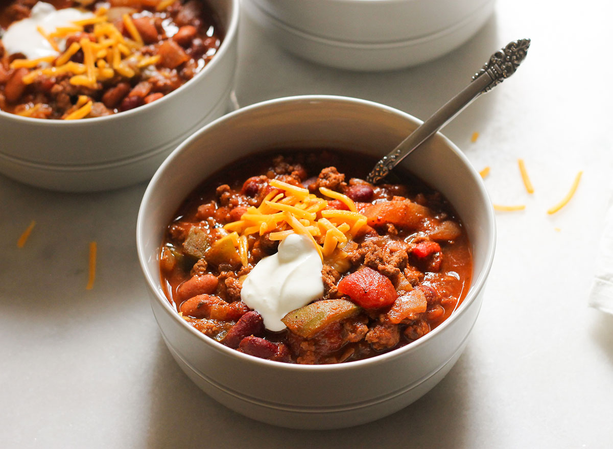 close up bowl of copycat wendy's chili with shredded cheese and sour cream