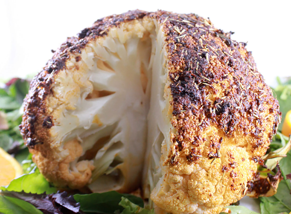 roasted cauliflower head with slice missing on bed of greens