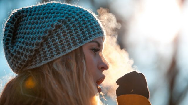 Woman breathing on her hands to keep them warm at cold winter day