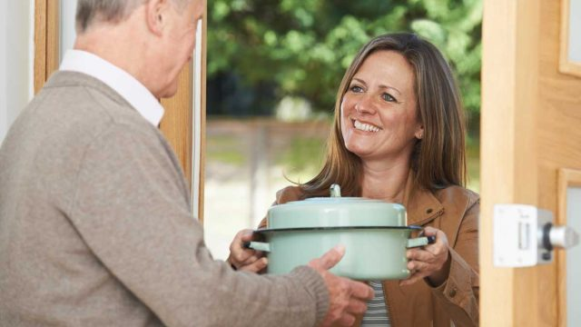 Woman bringing dish to family home