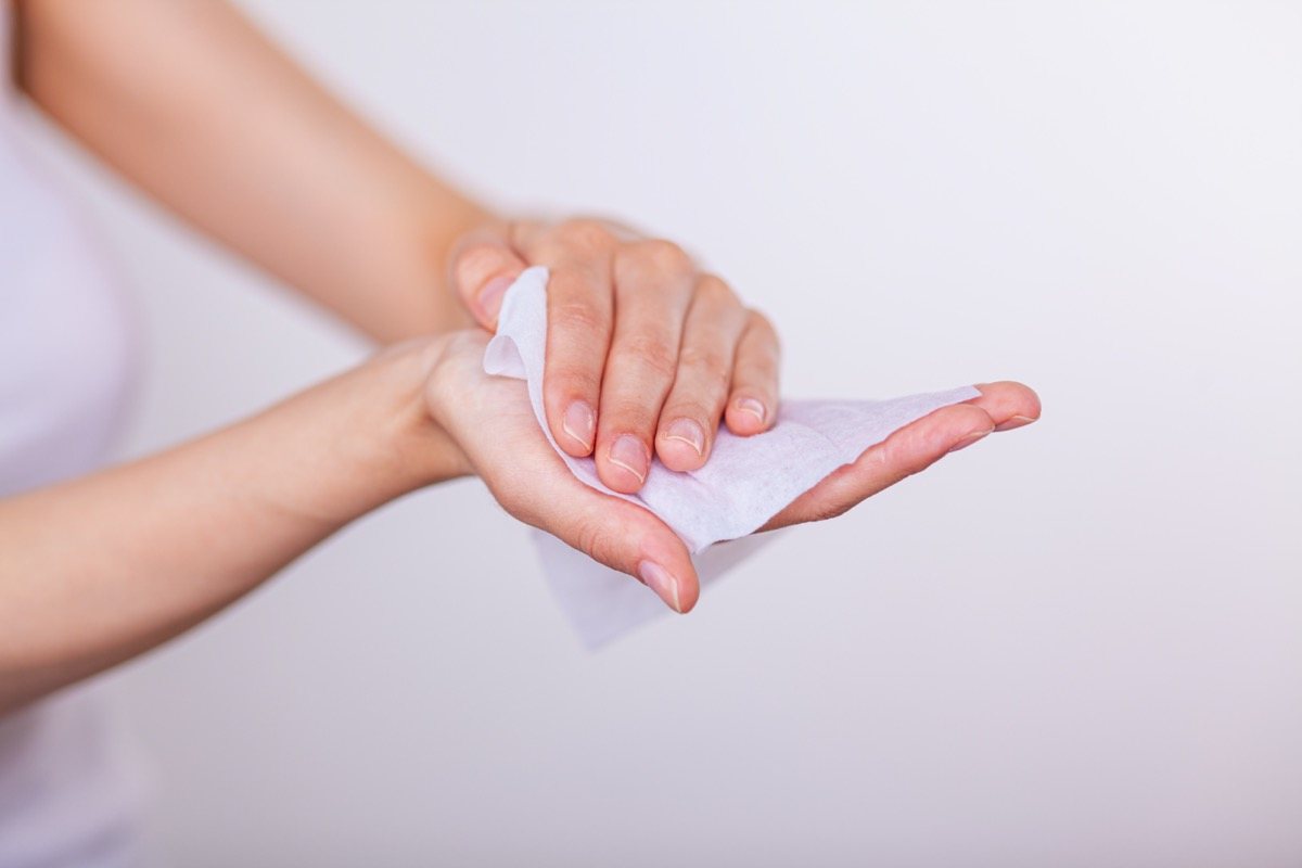 woman cleaning hands with wet wipes