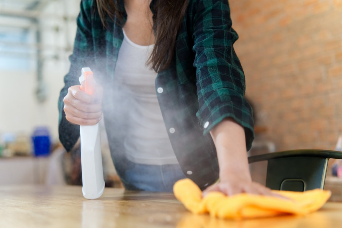 woman cleaning a house. She is wiping dust using a spray and a orange fabric while cleaning on the table
